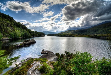 Killarney National Park (Irish: Páirc Náisiúnta Chill Airne) is located beside the town of Killarney, County Kerry, Ireland. It was the first national park established in Ireland, created when Muckross Estate was donated to the Irish state in 1932. The park has since been substantially expanded and encompasses over 102.89 km2 (25,425 acres) of diverse ecology, including the Lakes of Killarney, Oak and Yew woodlands of international importance, and mountain peaks. It has Ireland's only native herd of Red Deer and the most extensive covering of native forest remaining in Ireland. The park is of high ecological value because of the quality, diversity, and extensiveness of many of its habitats and the wide variety of species that they accommodate, some of which are rare. The park was designated a UNESCO Biosphere Reserve in 1981. The park forms part of a Special Area of Conservation. Killarney National Park is one of the very few places in Ireland that has been continuously covered by woodland since the end of the most recent glacial period,] approximately 10,000 years ago. Humans have lived in the area since at least the Bronze Age, approximately 4,000 years ago. Archaeologists have found evidence that copper mining took place in the Ross Island area during this period, which suggests that the area was of considerable importance to Bronze Age people. The park has many archaeological features, including a well preserved stone circle at Lissivigeen.